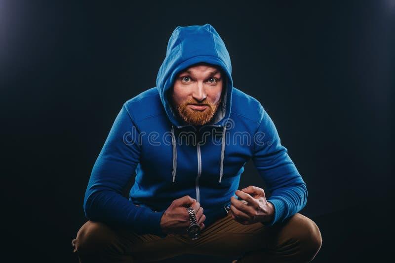 年轻有胡子的男性恶霸坐黑背景 免版税库存照片