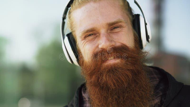 年轻有胡子的行家人特写镜头画象有耳机的听音乐和微笑对城市街道 图库摄影