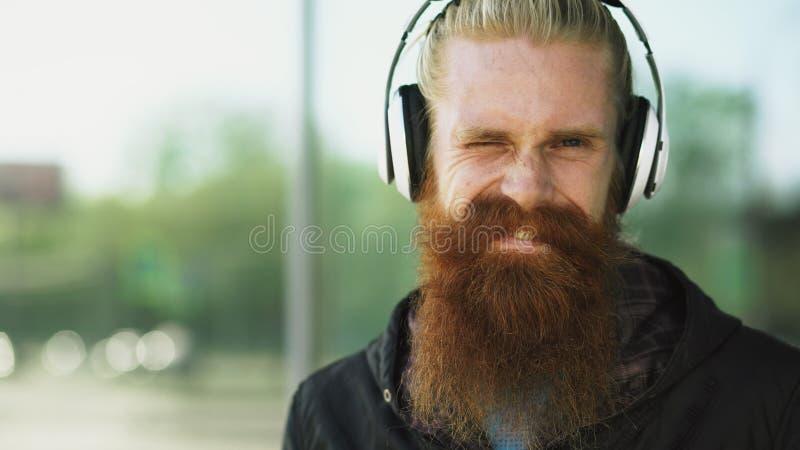 年轻有胡子的行家人特写镜头画象有耳机的听音乐和微笑对城市街道 库存照片