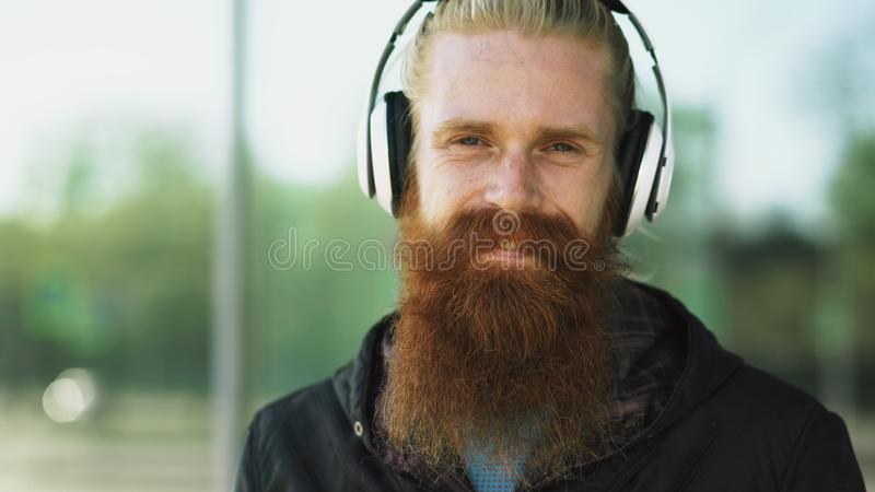 年轻有胡子的行家人特写镜头画象有耳机的听音乐和微笑对城市街道 免版税库存照片