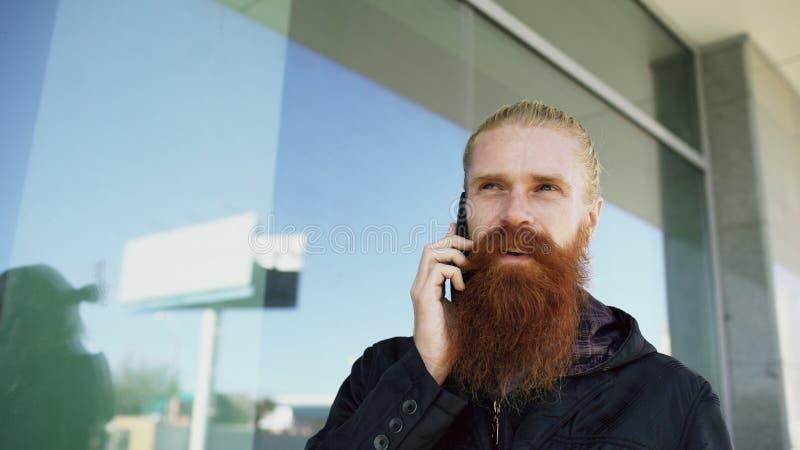 年轻有胡子的行家人被集中的谈话在citystreet的电话和有交谈在办公楼附近 免版税库存图片