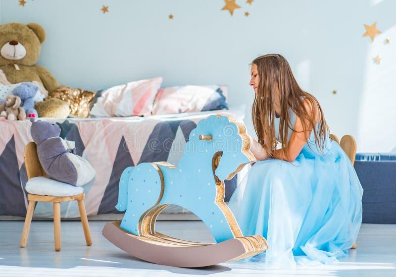 年轻有长发的少年深色的女孩在蓝色礼服坐与儿童的玩具的椅子在她的卧室和戏剧 免版税库存照片