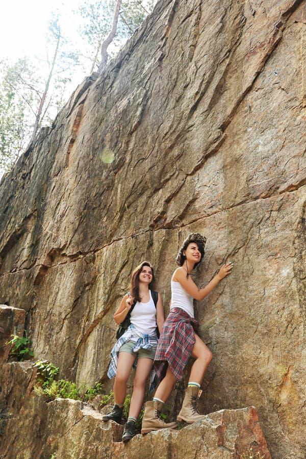 年轻朋友在夏日临近峭壁 免版税库存照片
