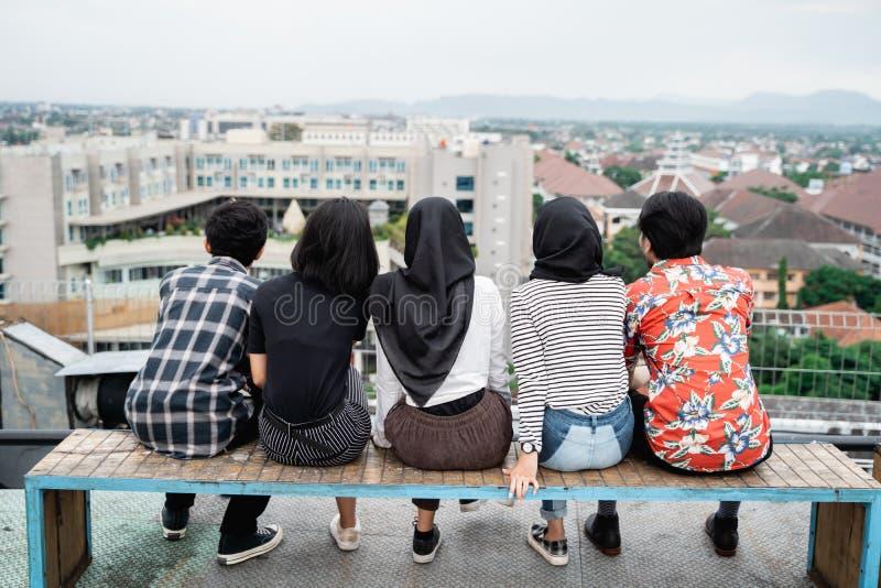 年轻朋友背面图一起坐屋顶 免版税库存照片