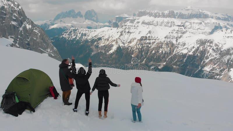 年轻朋友设置了在一个山和身分在-弹吉他的一个人-白云岩之外,意大利的一个帐篷 库存图片