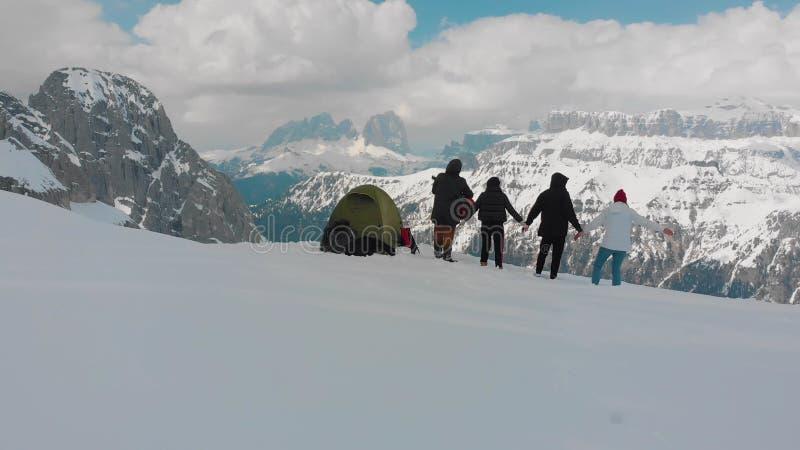 年轻朋友设置了在山的一个在握手之外-弹吉他的一个人的帐篷和身分-白云岩,意大利 免版税库存照片