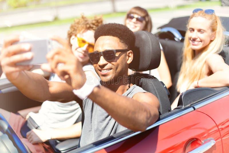 年轻朋友采取在敞蓬车汽车的一selfie 免版税库存图片
