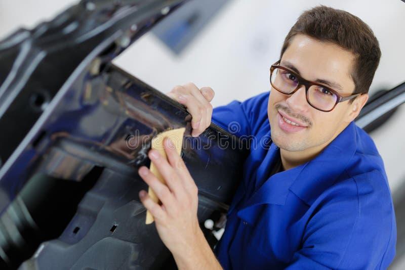 年轻服务技工清洗的汽车车门 免版税库存图片