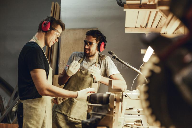 年轻木匠讲话在工作凳附近 免版税图库摄影