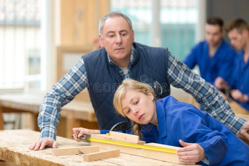 年轻木材加工学徒测量的木头 库存照片