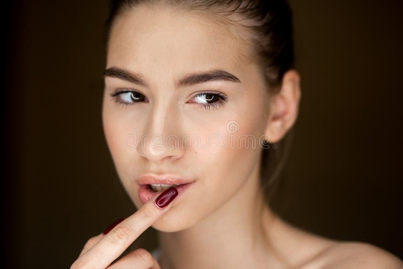 年轻棕色毛发的女孩画象有握她的在她的面孔的自然构成的手指 免版税库存照片