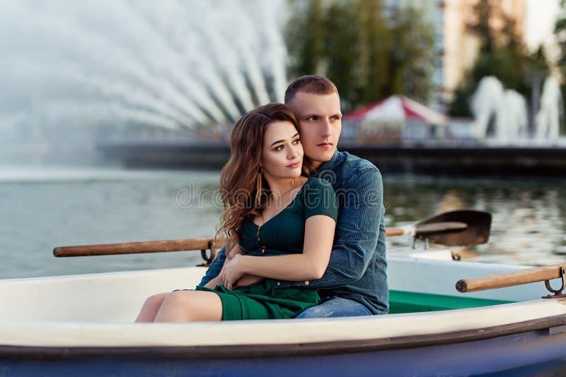 年轻欧洲夫妇是在湖的划船,年轻人,并且他的女朋友坐入小船在日落,在爱的夫妇 免版税库存照片