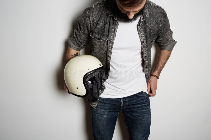 年轻残酷有胡子的男性模型在黑衬衣牛仔裤和空白白色T恤优质夏天棉花摆在,在白色 库存图片
