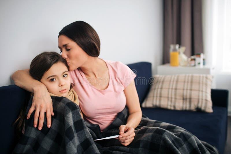 年轻母亲与女儿一起坐长沙发在屋子里 她亲吻她的头发和容忍孩子 Mothere举行温度计 免版税库存图片