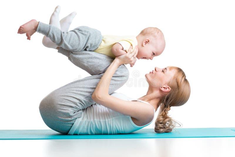年轻母亲与男婴一起做健身锻炼被隔绝 免版税库存照片
