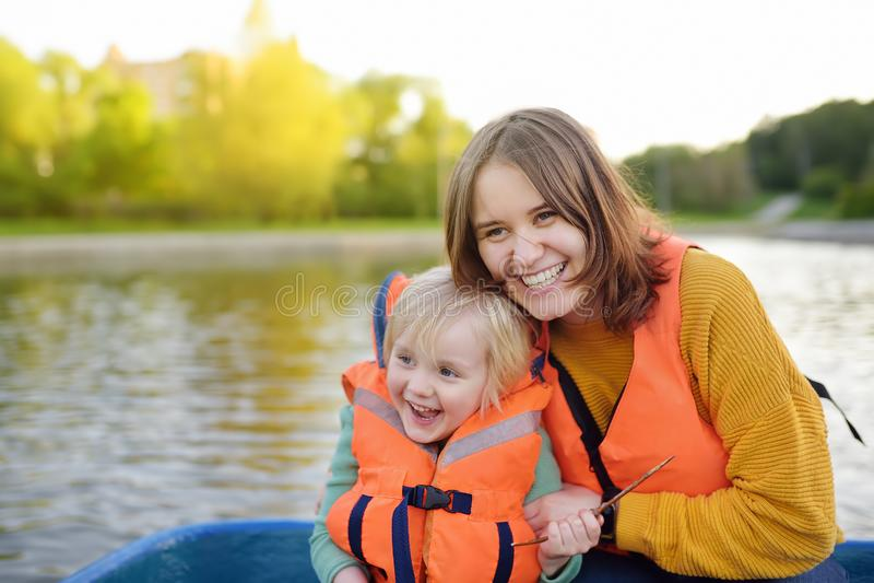 年轻母亲和一点儿子划船在一个河或池塘晴朗的夏日 质量一起家庭时间在自然 免版税库存图片