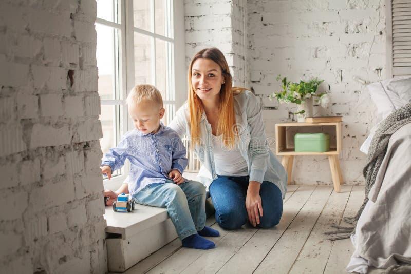 年轻母亲和儿子使用 妇女和儿童男孩在家 免版税库存照片