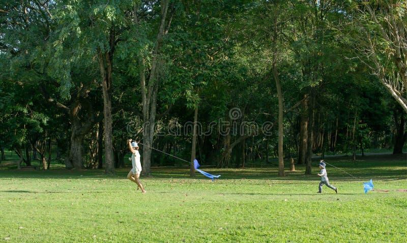 年轻母亲和儿子开始在绿色草甸的风筝夏日 免版税库存图片