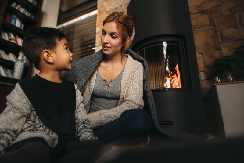 年轻母亲和儿子由壁炉在家 库存照片