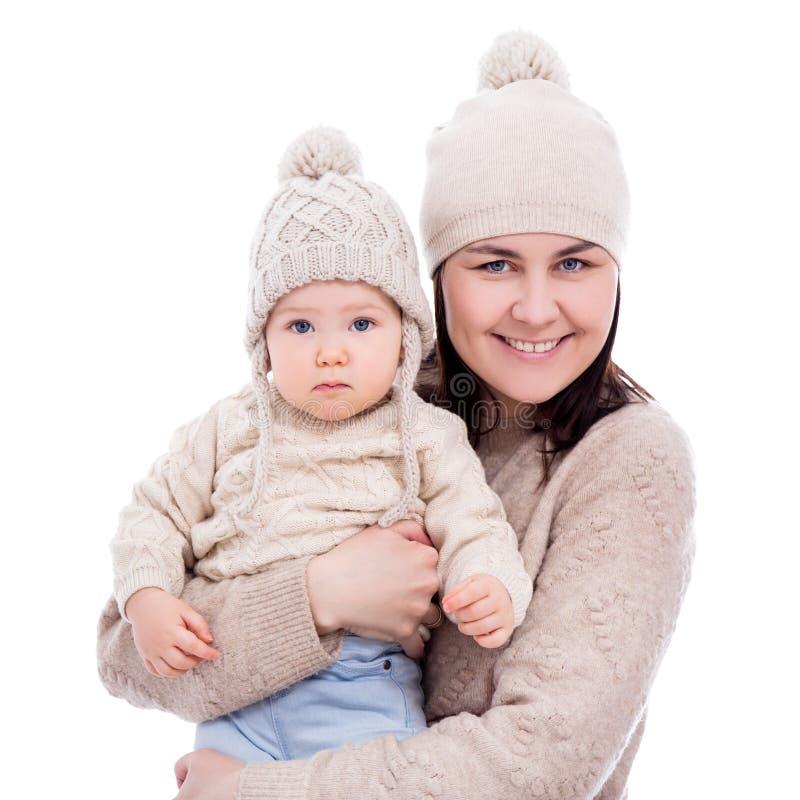年轻母亲和可爱宝贝女孩画象在白色隔绝的冬季衣服的 免版税图库摄影