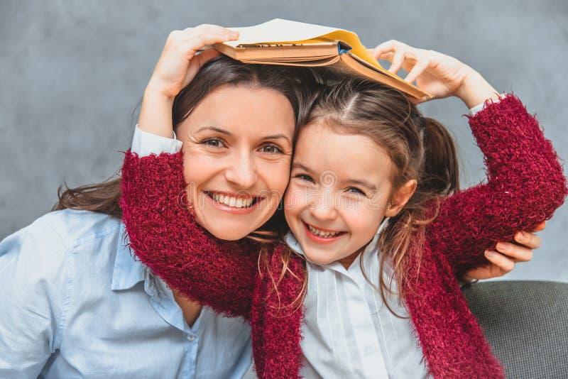 年轻母亲和女儿灰色背景的 恳切微笑的拥抱和调查照相机 在此期间, 免版税图库摄影