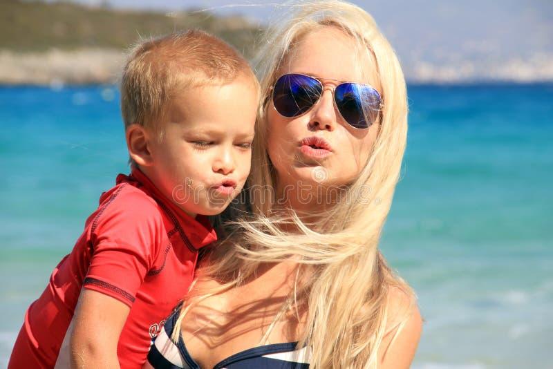 年轻母亲和她的孩子一起演奏和获得乐趣在海海滩在暑假时间 与孩子的假日, 免版税库存照片