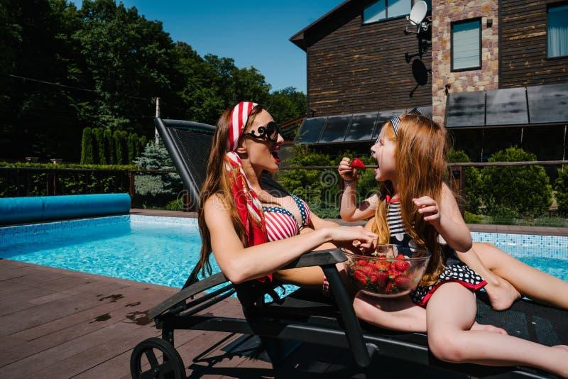 年轻母亲和她的小女儿在游泳池附近 免版税库存图片