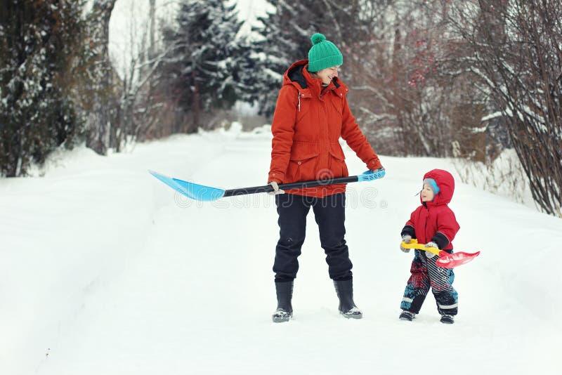年轻母亲和她的小孩儿子立场与雪铁锹在农村路 冬天季节性概念 免版税库存照片