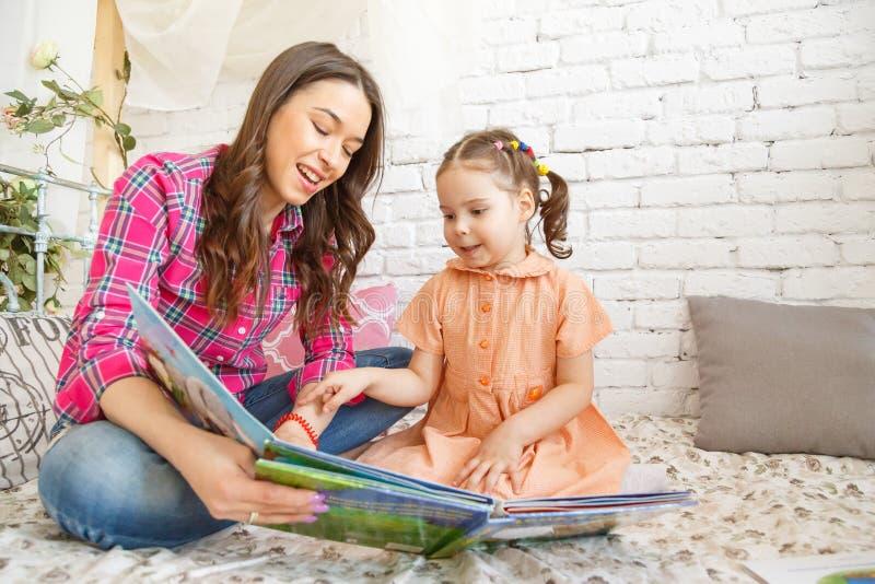年轻母亲和她的读书的儿童女孩 免版税库存图片