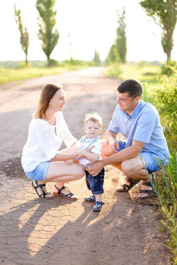 年轻母亲和父亲坐有一点婴孩的路,阳光天气 库存图片