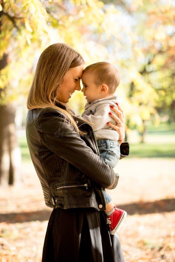 年轻母亲和男婴在秋天停放 免版税图库摄影