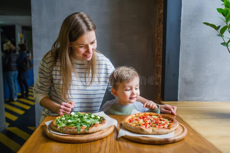 年轻母亲和逗人喜爱的矮小的儿子吃比萨在餐馆 免版税库存照片