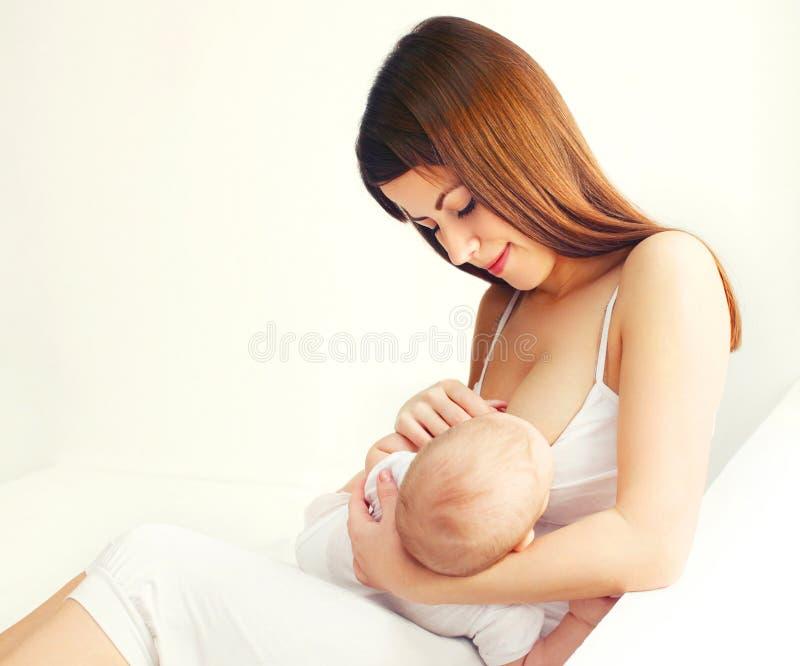年轻母亲哺养的乳房她的婴孩在家 库存图片