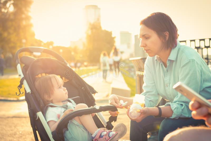 年轻母亲喂养婴儿车的儿童女孩 免版税库存图片