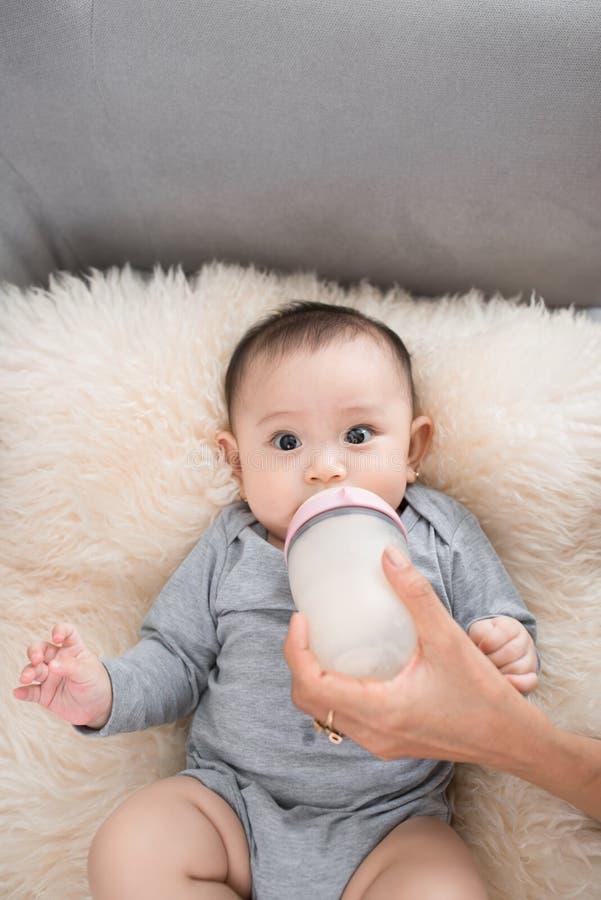 年轻母亲在室喂养她的婴孩 免版税库存照片