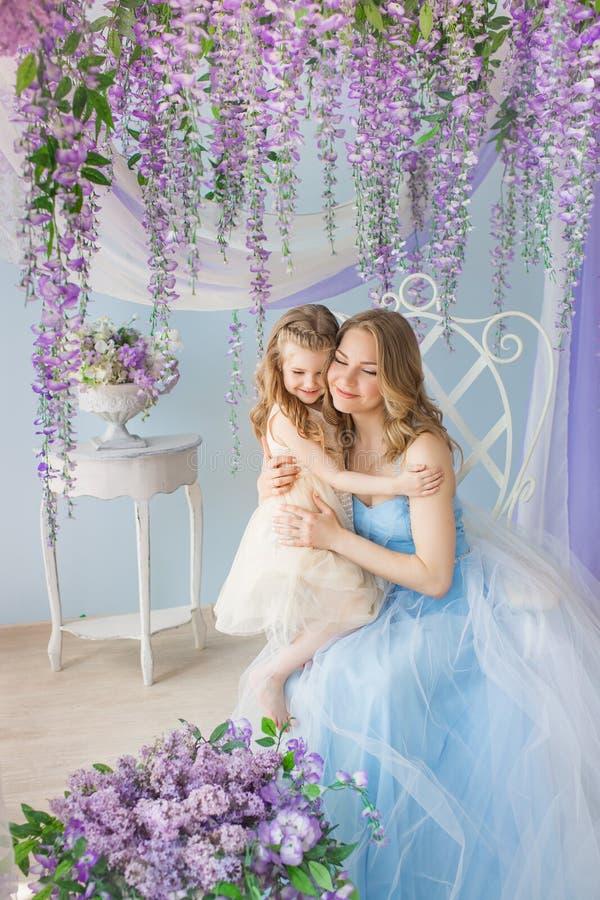 年轻母亲在演播室拥抱她的小女儿装饰了丁香花 库存照片