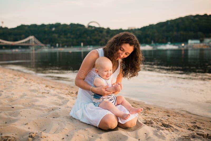 年轻母亲坐与一岁的小儿子的海滩 拥抱的男孩,微笑,笑,夏日 无忧无虑愉快的童年 库存图片