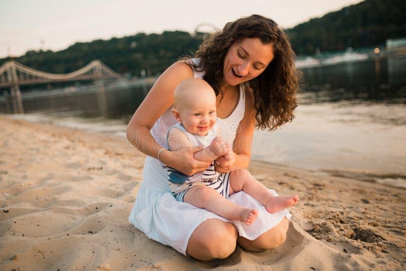 年轻母亲坐与一岁的小儿子的海滩 拥抱的男孩,微笑,笑,夏日 无忧无虑愉快的童年 图库摄影
