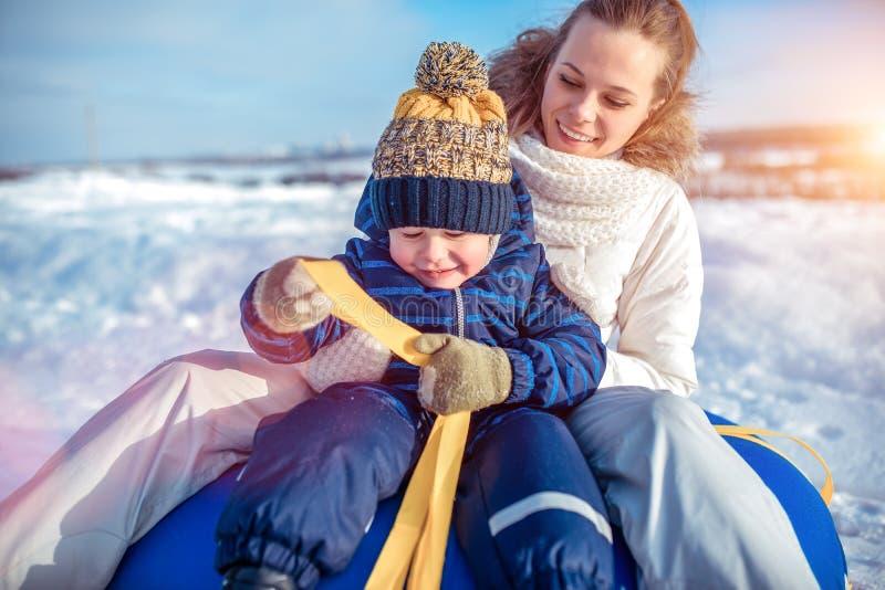 年轻母亲妇女愉快微笑,坐有她的儿子男孩的管材3-6岁,演奏scrabing在冬天 休息 免版税库存照片