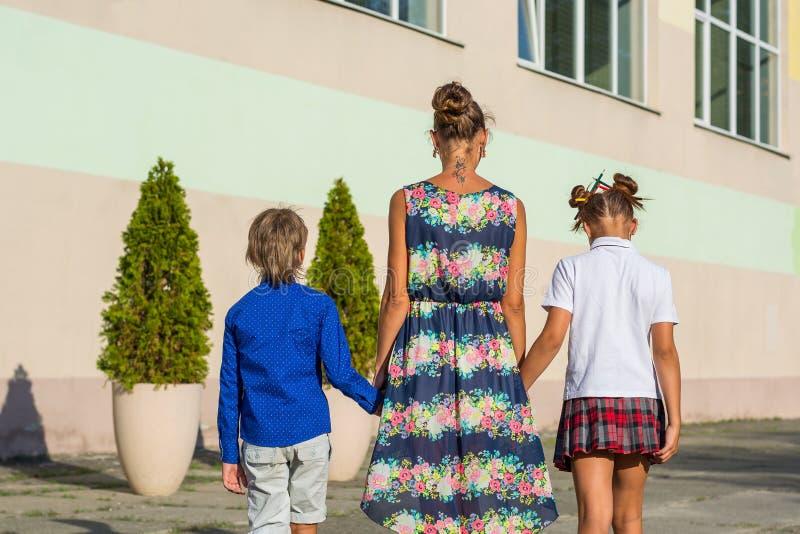 年轻母亲带领她的女儿和儿子学校 免版税库存图片