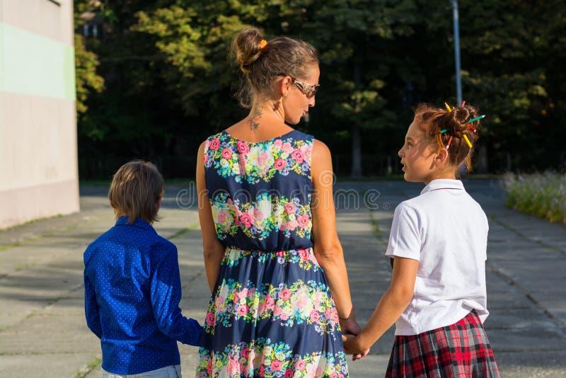 年轻母亲带领她的女儿和儿子学校 库存照片