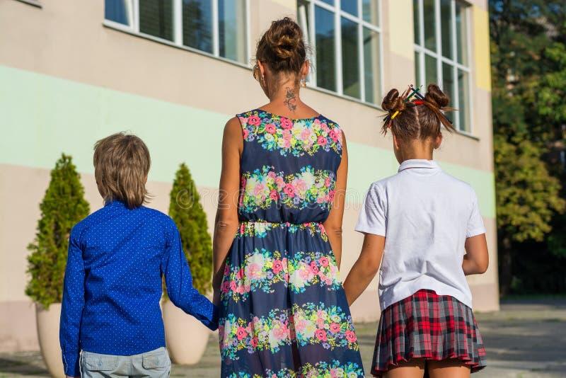 年轻母亲带领她的女儿和儿子学校 免版税库存照片
