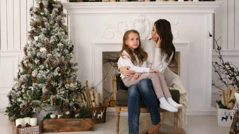 年轻母亲谈话在有有一点乏味女儿的电话坐她的膝部在xmas树旁边 免版税库存图片