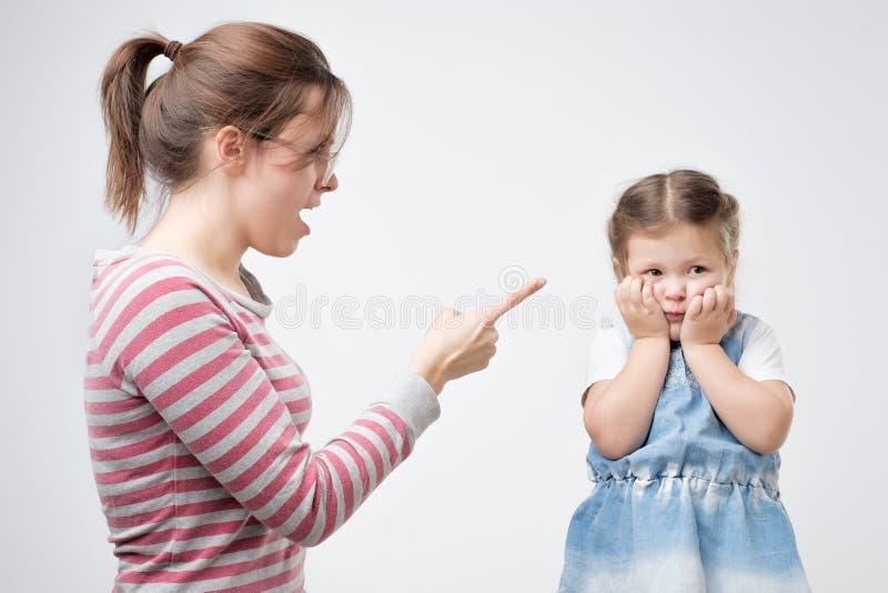 年轻母亲责骂她的女儿 盖她的面孔的小女孩用手 免版税库存图片