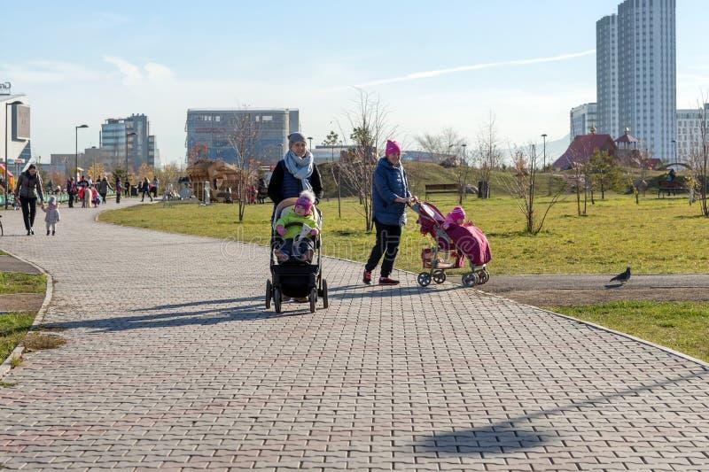 年轻母亲走与小孩子在一个公园里,克拉斯诺亚尔斯克市的背景的 库存图片
