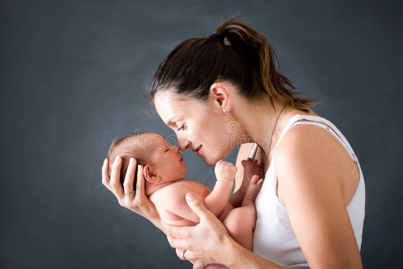年轻母亲,亲吻和拥抱她新出生的男婴 图库摄影
