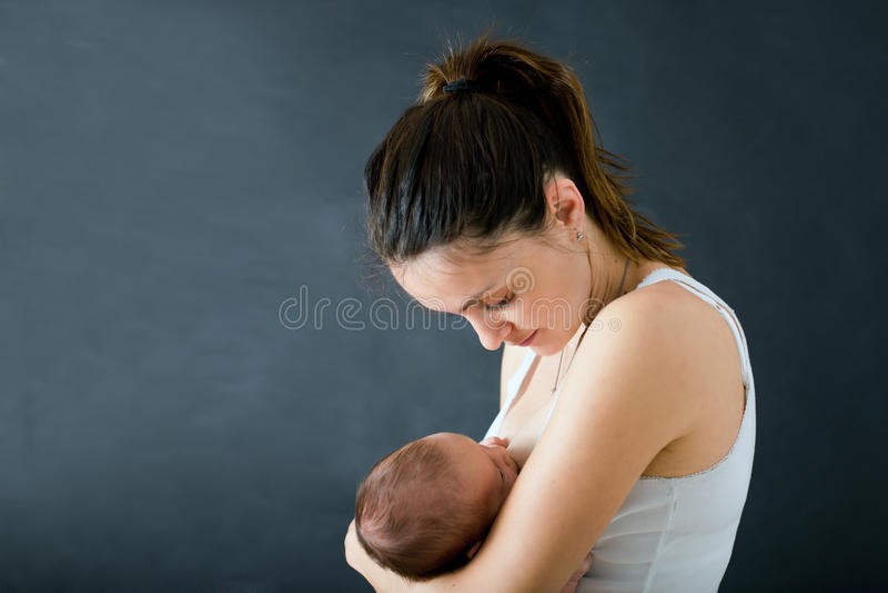 年轻母亲,哺乳她新出生的男婴 库存照片