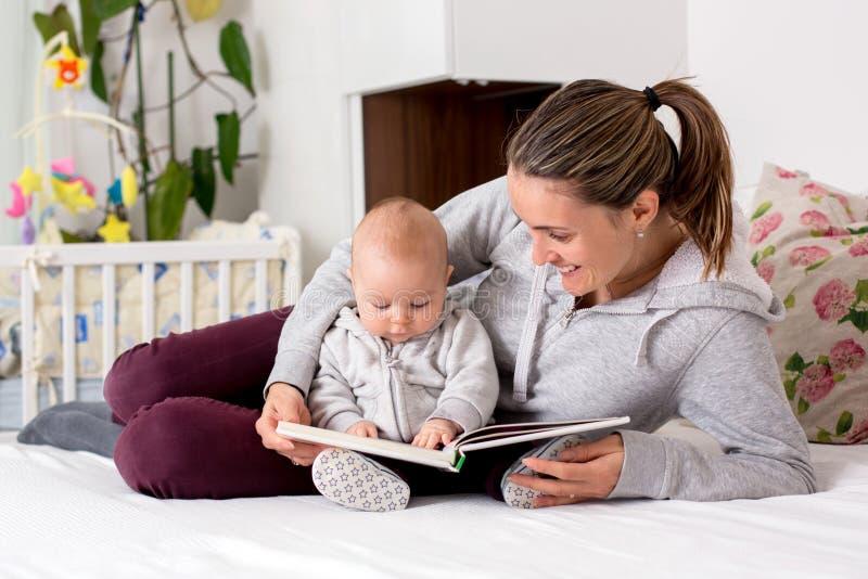 年轻母亲,读书对她的男婴,显示他pictur 免版税库存照片