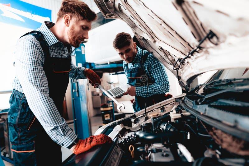 年轻汽车机械师修理有板钳的汽车 库存照片