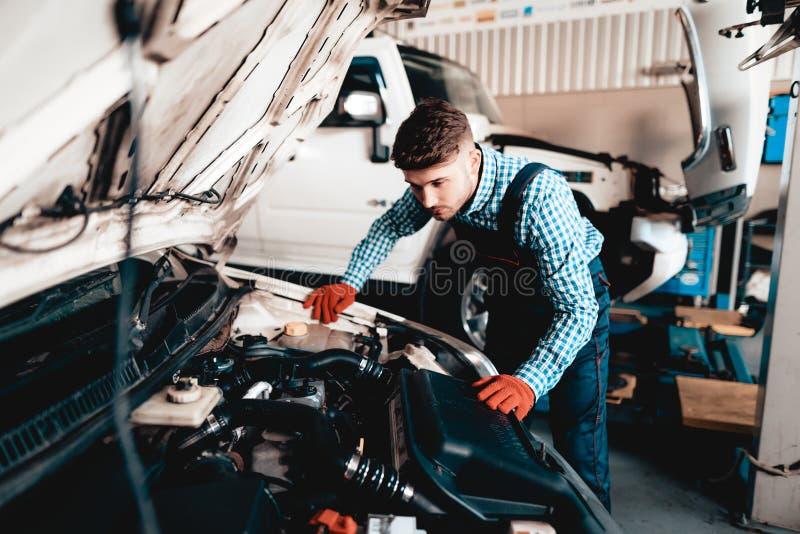年轻汽车机械师看在敞篷下 库存图片